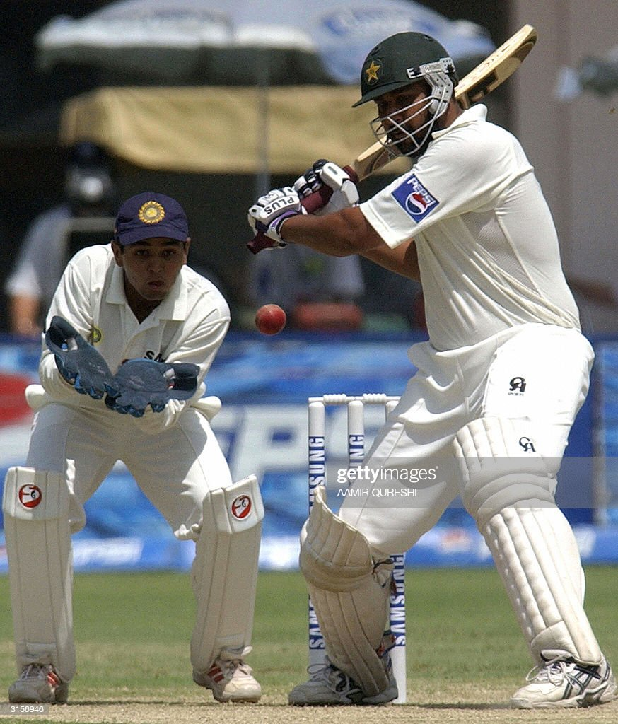 Pakistani captain Inzamam-ul Haq (R) hits a boundary off Indian part time bowler Sachin Tendulkar (unseen) during the third day of the first test match between Pakistan and India in Multan, 30 March 2004. Pakistan were 137-2 before lunch still needing 339 to avoid the follow-on. AFP PHOTO/Aamir QURESHI