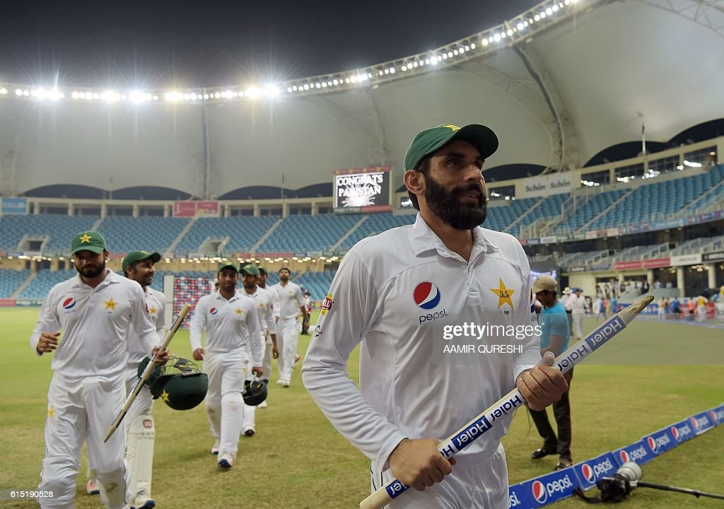 Pakistani captain Misbah-ul-Haq (R) and his teammate Azhar Ali (L) hold the wickets as they head back to the pavilion after winning the first day-night Test between Pakistan and the West Indies at the Dubai International Cricket Stadium in the Gulf Emirate on October 17, 2016. Pakistan beat West Indies by 56 runs in the first day-night Test on the fifth and final day in Dubai on October 17, taking a 1-0 lead in the three-match series. / AFP / AAMIR