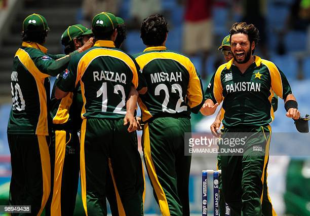 Pakistani captain Shahid Afridi celebrates with teammates after making a catch to take the wicket of South African batsman Graeme Smith during the...