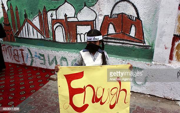 Pakistani child covering her mouth holds a banner during a demonstration in Karachi Pakistan on December 18 to condemn Taliban assault on an armyrun...
