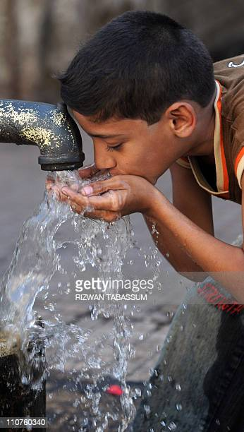 A Pakistani child drinks water from a handpump in an impoverished neighbourhood of Karachi on March 22 on World Water Day According to UNICEF as many...