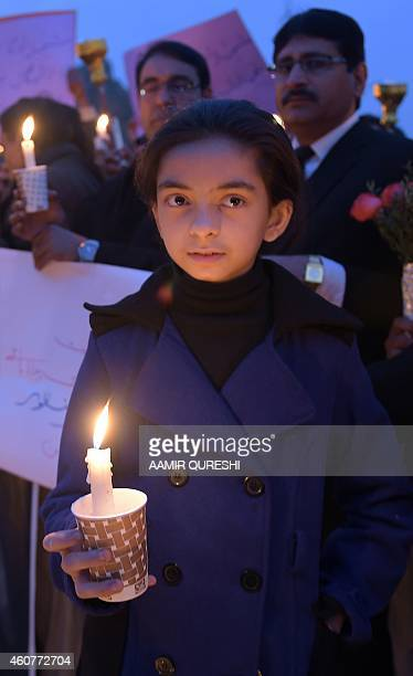 A Pakistani child poses holding a lighted candle with lawyers and civil society activists during a vigil in Islamabad on December 22 held for...
