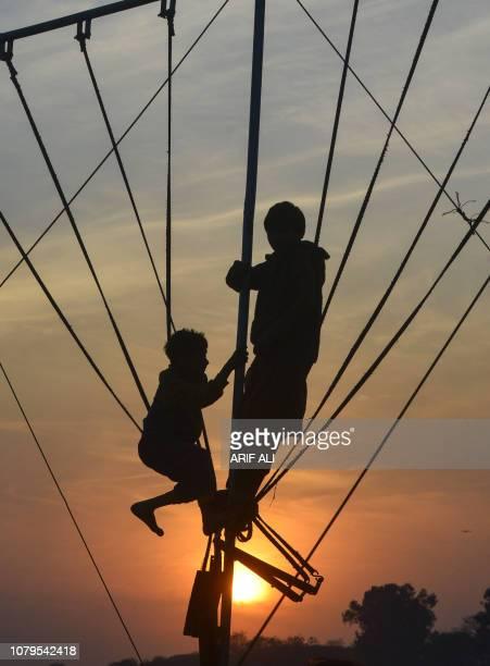 Pakistani children climb crossbar swings at sunset in Lahore on January 9 2019