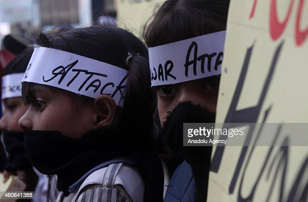 Pakistani children covering their mouths hold a demonstration in Karachi Pakistan on December 18 to condemn Taliban assault on an armyrun school in...