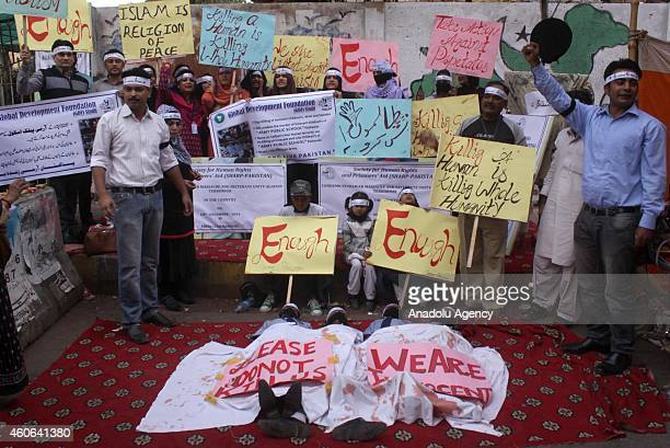 Pakistani children covering their mouths pretend dead during a demonstration in Karachi Pakistan on December 18 to condemn Taliban assault on an...