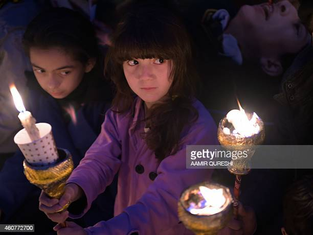 Pakistani children hold lighted candles during a vigil in Islamabad on December 22 held for schoolchildren and teachers killed in an attack by...
