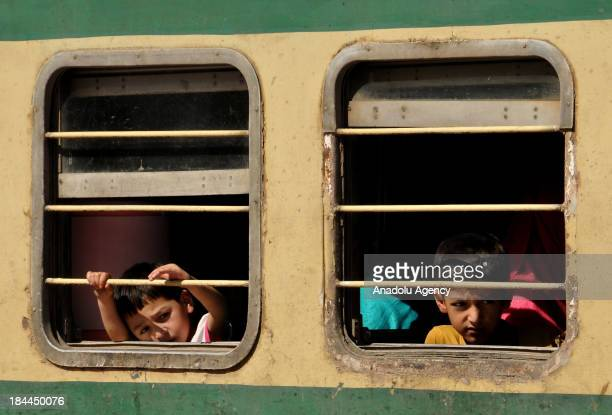 Pakistani children look out of a train window at the Railway Station on October 14 in Rawalpindi Pakistan after leaving their hometowns to celebrate...