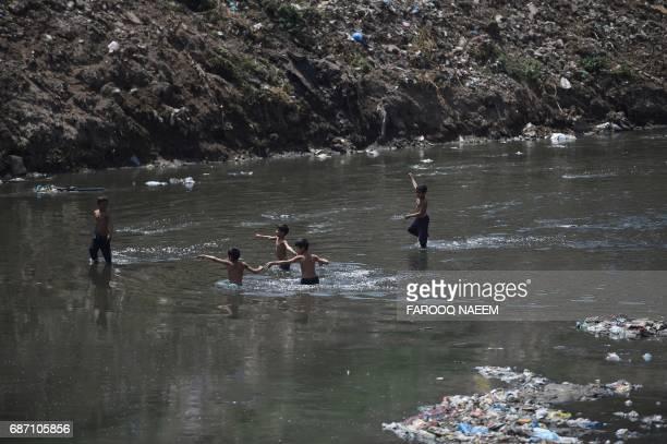 Pakistani children play in an open drain in Rawalpindi on May 23 2017 / AFP PHOTO / FAROOQ NAEEM