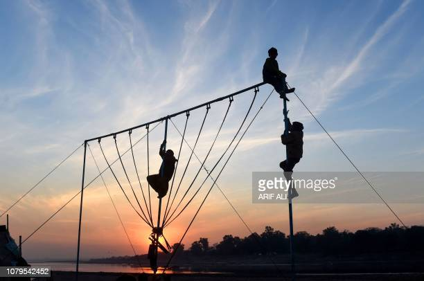 TOPSHOT Pakistani children play on crossbar swings at sunset in Lahore on January 9 2019