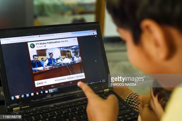 Pakistani children point at a computer screen showing a screen grab of a press conference attended by provincial minister Shaukat Yousafzai and...