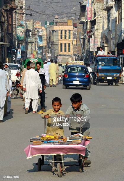 Pakistani children push a cart at a market in Mingora on October 11 the hometown of education activist Malala Yousafzai Friends and supporters of...