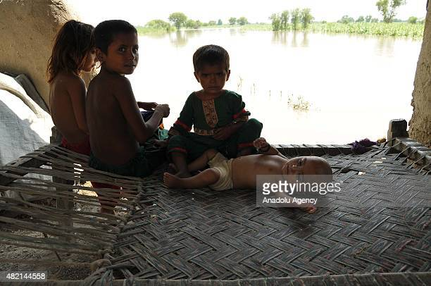 Pakistani children sit on a sofa as their house was inundated in floodwater at Rajanpur district of Punjab province in Pakistan on July 27 2015...
