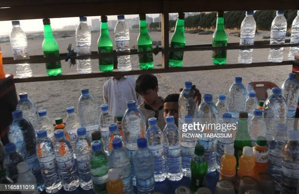 Pakistani children stand in front of a beverage stand on a beach in Karachi on March 21 2012 on the eve of the UN World Water Day More than 25...