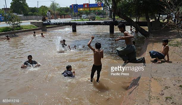 Pakistani children take a bath in a canal to beat the heat during hot weather in Lahore