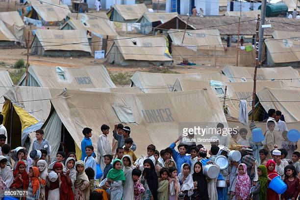 Pakistani children wait for hours in line for dinner at the Yar Hussain camp June 1 2009 in Swabi Pakistan According to the NWFP authorities and the...