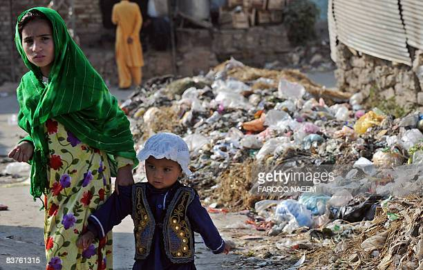 Pakistani children walk past a pile of garbage on a street in Rawalpindi on November 19 2008 Pakistani government launched an action plan keeping in...