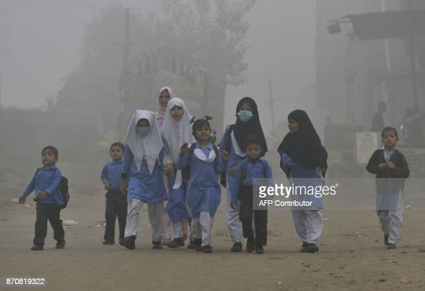 Pakistani children walk to school in heavy smog in Lahore on November 6 2017 / AFP PHOTO / ARIF ALI