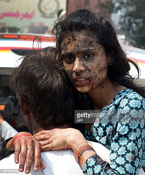 Pakistani Christian carries an injured woman on her arrival at the hospital after two suicide bomb attacks on a Church in Peshawar on September 22,...