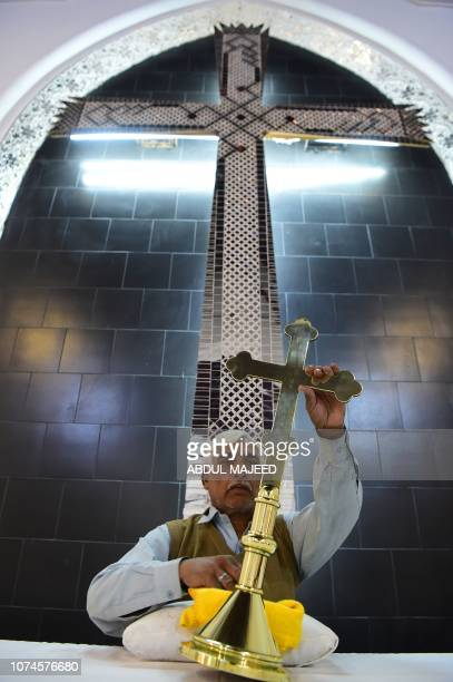 A Pakistani Christian cleans a cross at the St John's Church ahead of Christmas celebrations in Peshawar on December 22 2018