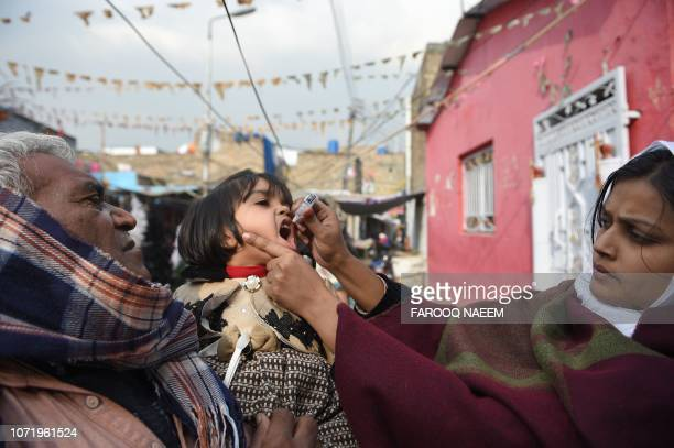 A Pakistani Christian health worker administers polio vaccine drops to a child during a polio vaccination campaign in a Christian colony in Islamabad...