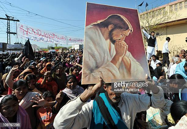 Pakistani Christian mourners march as they shout slogans against the killing of slain Pakistani minister for minorities Shahbaz Bhatti during the...