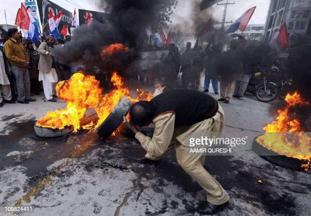 A Pakistani Christian sets tyres on fire as others shout slogans against the killing of Christian government minister Shahbaz Bhatti in Islamabad by...
