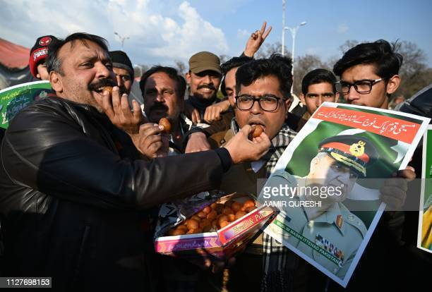 Pakistani Christians carry a poster featuring an image of Pakistani Army Chief General Qamar Javed Bajwa as they offer sweets to each other in...