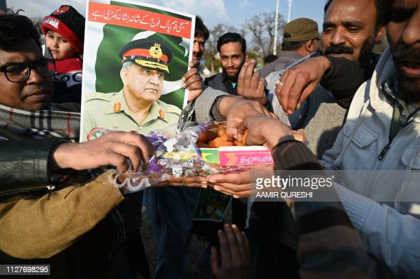 Pakistani Christians carry poster featuring image of Pakistani Army Chief General Qamar Javed Bajwa as they eat sweets in Islamabad on February 27...