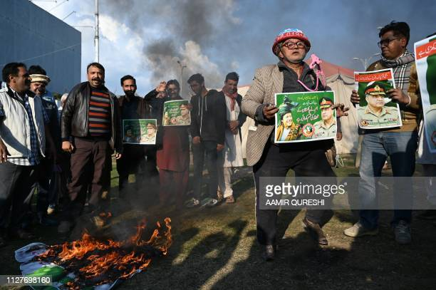 Pakistani Christians carry posters featuring images of Pakistani Army Chief General Qamar Javed Bajwa beside a burning Indian flag during a protest...
