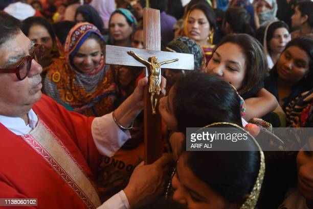 Pakistani Christians devotees kiss a depiction of the crucifixion of Jesus during a Good Friday service at St Anthony's church in Lahore on April 19...
