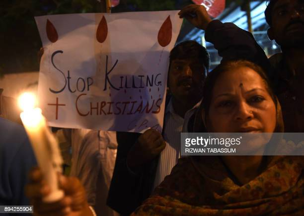 TOPSHOT Pakistani Christians hold banners and lighted candles during a protest in Karachi on December 17 after a suicide bomber attack on a church in...