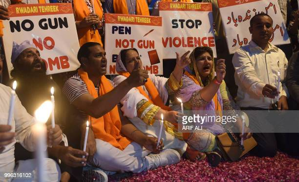 Pakistani Christians hold candles and placards during a vigil for the overnight blast victims in Lahore on July 11 2018 Thousands flocked to the...