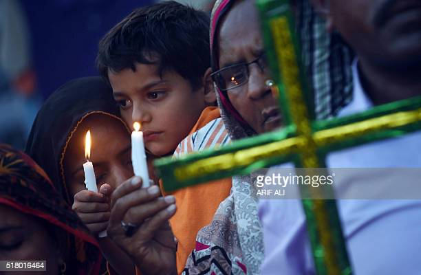 TOPSHOT Pakistani Christians hold candles as they stage a rally in Lahore on March 29 to pay tribute for the victims of a suicide bomb blast Taliban...