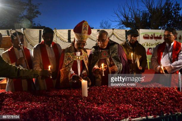Pakistani Christians priest light candles for the victims of suicide attack on a Church in Quetta on December 22 2017 A suicide bomb attack on a...