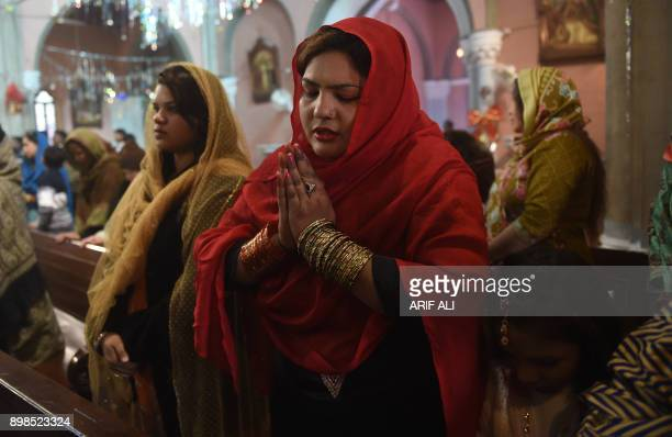Pakistani Christians take part in Christmas Day mass at a church in Lahore on December 25 2017 / AFP PHOTO / ARIF ALI