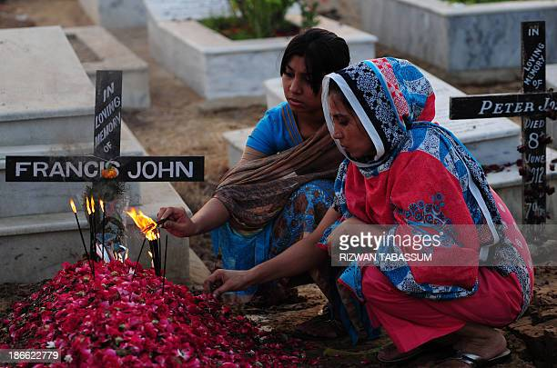 Pakistani Christians visit the grave of a relative at the Catholic cemetery during All Souls Day in Karachi on November 2 2013 All Souls Day is...