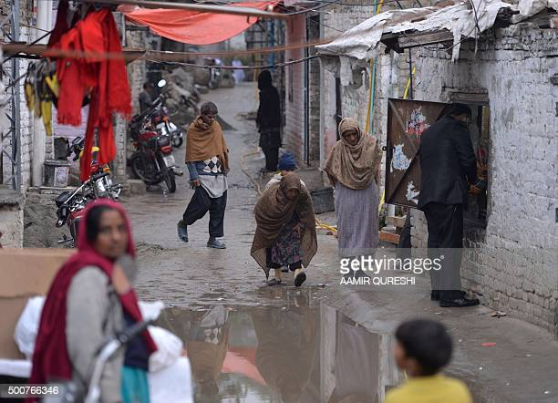 Pakistani Christians walk down a street in a slum Christian neighborhood in Islamabad on December 10 2015 Human rights activists slammed Islamabad...