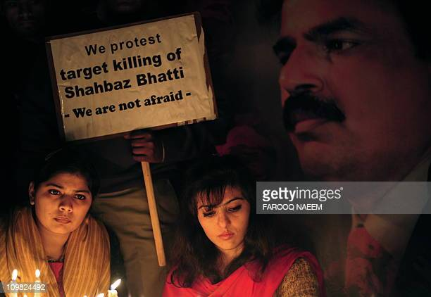 Pakistani civil rights activists light candle during a ceremony on the attack site of slain minority affairs minister Shahbaz Bhatti in Islamabad on...