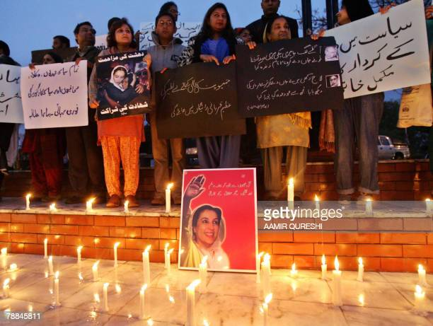 Pakistani civil rights activists stand beside lit candles to pay tribute to slain opposition leader Benazir Bhutto during a rally in Islamabad 09...
