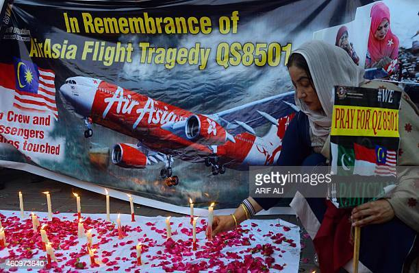 A Pakistani civil society activist places a candle during a vigil for the victims of AirAsia Flight 8501 in Lahore on January 2 2015 Indonesian...