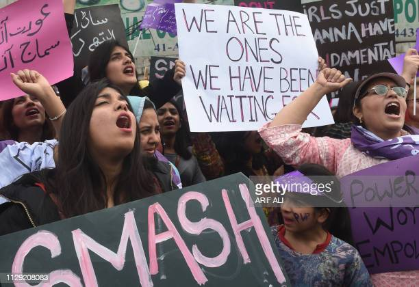 Pakistani civil society activists carry placard and shout slogans during a rally for women rights on International Women's Day in Lahore on March 8...