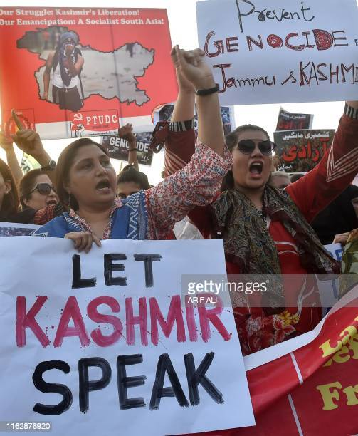 Pakistani civil society activists carry placards as they shout slogans during a protest rally in Lahore on August 20 as they condemn the India...