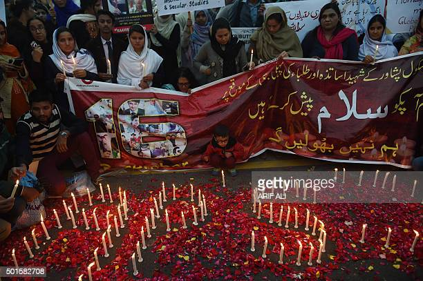 Pakistani civil society activists gather around lighted candles in Lahore on December 16 on the first anniversary of an attack on Army Public School...
