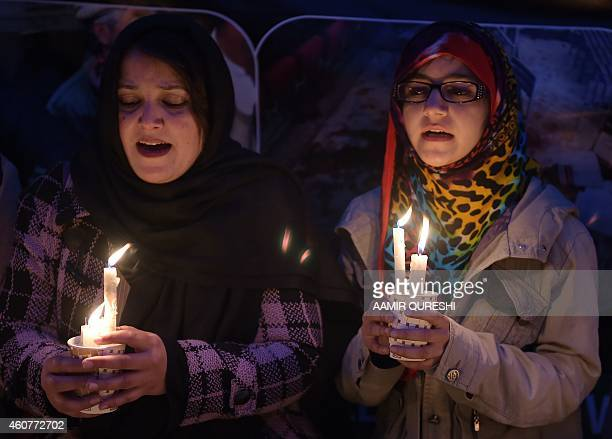Pakistani civil society activists hold lighted candles during a vigil in Islamabad on December 22 held for schoolchildren and teachers killed in an...