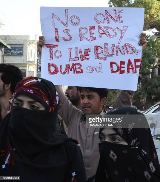 Pakistani civil society members and university students wave placards and shout slogans as they take part in a protest against the killing of Mashal...