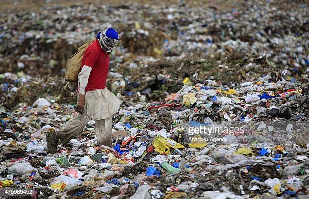 Pakistani collects usable material from a dump site on the World Environment Day in Islamabad Pakistan on June 5 2015 World Environment Day is...