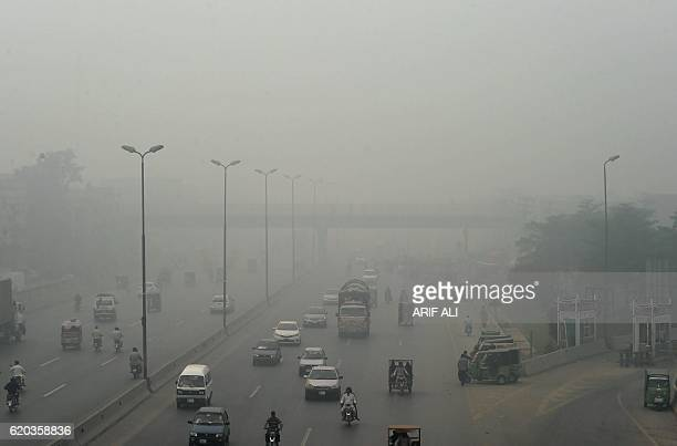 Pakistani commuters are seen on a street during a smoggy day in Lahore on November 2 2016 The Pakistan Meteorological Department has forecast...