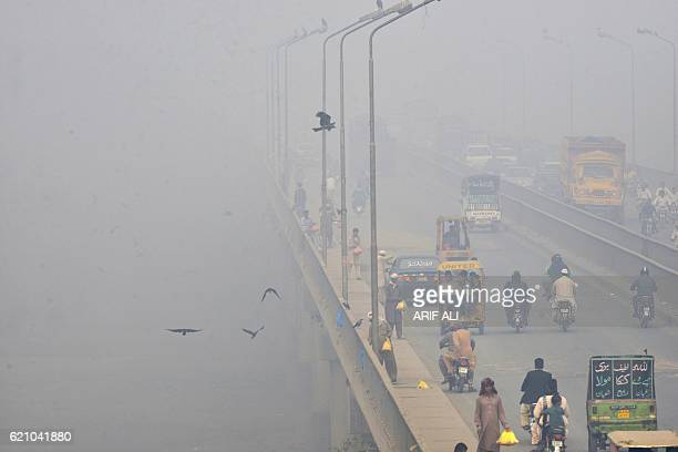 Pakistani commuters cross a bridge as heavy smog envelops the city in Lahore on November 4 2016 The Pakistan Meteorological Department has forecast...