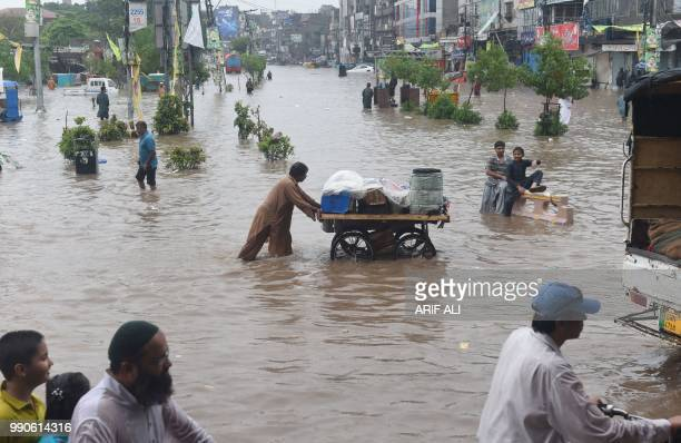 Pakistani commuters cross a flooded street after heavy rains in Lahore on July 3 2018