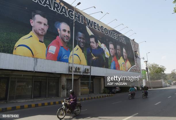 Pakistani commuters drive past a billboard featuring images of players ahead of the Pakistan Super League cricket match in Karachi on March 20 2018...